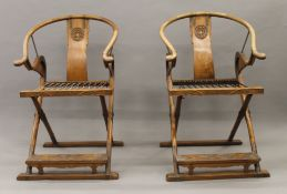 A pair of late 19th/early 20th century Chinese brass mounted carved elm folding open armchairs.
