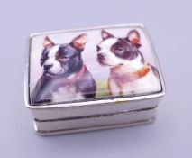 A silver pill box depicting dogs. 3 cm wide.