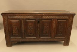 An 18th century carved four panel oak coffer. 146 cm long.