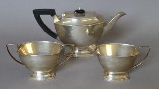 A silver three-piece tea set. The teapot 28 cm long. 933.6 grammes total weight.