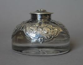 A silver mounted inkwell embossed with cherubs. 6 cm high.