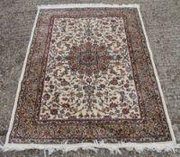 An ivory ground full pile Kashmir shorbass medallion design rug.