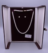A single strand pearl necklace with matching earrings. Necklace 41 cm long.