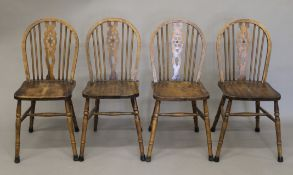 A set of four wheelback chairs.