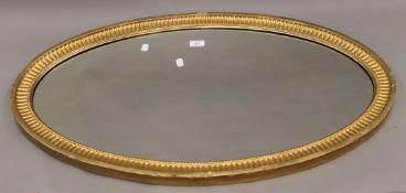 A 19th century oval gilt framed mirror. 90 cm wide, 53 cm high, 3.5 cm deep.