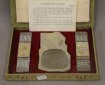 A boxed Chinese calligraphy set. The box 24 cm wide.