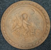 A large terracotta plaque depicting putto riding a dolphin. 55 cm diameter.