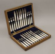 A cased set of mother-of-pearl and silver knives and forks.
