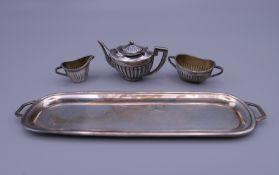 A miniature silver tea set on tray. Tray 13.5 cm long, teapot 3 cm high. 29.7 grammes.