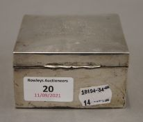A silver cigarette box. 8.5 cm wide. 279.7 grammes total weight.