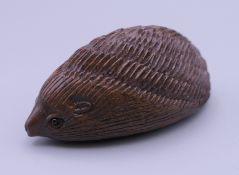A wooden netsuke formed as a hedgehog. 5 cm long.