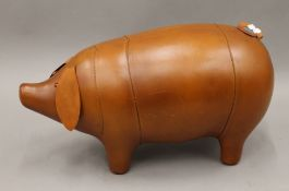 A leather pig footstool. 66 cm long.