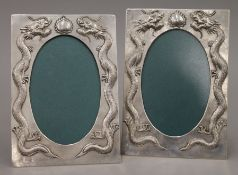 A pair of Chinese silver frames decorated with dragons, with makers mark of Zeewo. 13 x 18.75 cm.