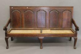 An 18th century oak panelled back settle.