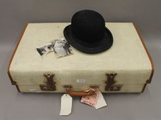 A vintage suitcase and a bowler hat. Approx size 7.25.