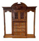 A Victorian carved burr oak compactum wardrobe. 228 cm high x 245 cm wide.