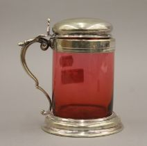 A cranberry glass and silver plated tankard. 14 cm high.