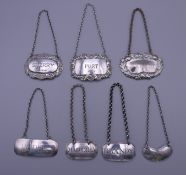 A collection of silver and silver plated decanter labels.