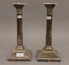 A pair of silver Corinthian column candlesticks. Each 29.5 cm high.