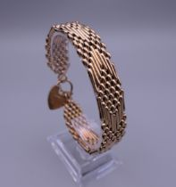 A 9 ct gold bracelet with padlock fastener. Approximately 18.5 cm long. 27 grammes.