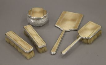 A silver and enamel dressing table set.