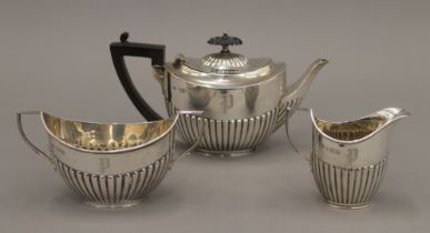 A silver three-piece tea set. The teapot 11 cm high. 12.8 troy ounces total weight.