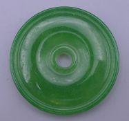 A green jade bi disc. 5.5 cm diameter.