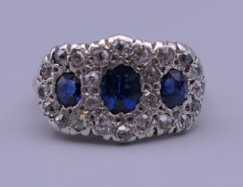 An unmarked gold, diamond and sapphire ring. Ring size O. 4.9 grammes total weight.