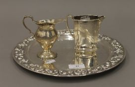 Two silver jugs and an embossed platter. The latter 29.5 cm diameter. 26.8 troy ounces.