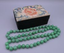A vintage Chinese box covered with silk embroidery containing a string of jade beads. The box 13.