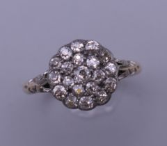 An 18 ct gold and diamond flowerhead ring. Ring size Q. 3.4 grammes total weight.