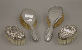 Four silver backed brushes.