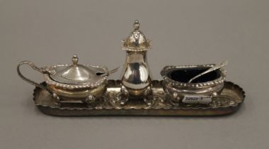 A silver three-piece cruet set and a silver pin tray. The latter 18.5 cm long. 6.7 troy ounces.
