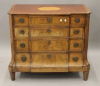 A 19th century inlaid mahogany breakfront chest of drawers. 96.5 cm wide.
