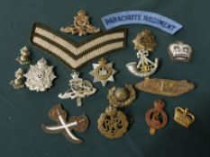 Collection of metal and cloth badges, mainly British, including paratrooper regiment shoulder