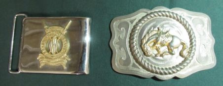 Metal belt buckle with a bucking bronco and a belt buckle with the badge of the Kenyan Prisons