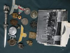 Collection of German WWII badges and insignia including a belt buckle, SS ring, eagle on Swastika