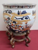 Japanese fishbowl, the exterior decorated in Imari pallette with trailing foliage, the interior with