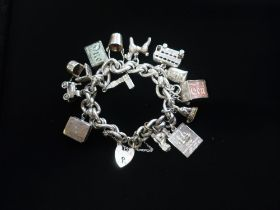 Silver charm bracelet with heart padlock clasp , charms include £1 and £10 notes, London bus, Big