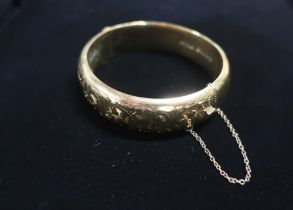 9ct gold hinged bangle with safety chain stamped 9ct 25.3g