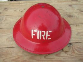 WWII steel red fire helmet with fire stencil to the front, leather liner and canvas chip strap