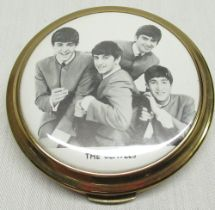 1960's The Beatles powder compact with central printed image of The Beatles in circular gilt case