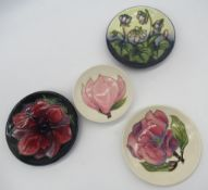 Three small Moorcroft circular dishes, D12cm, small Moorcroft saucer dish D9.5cm, all with various
