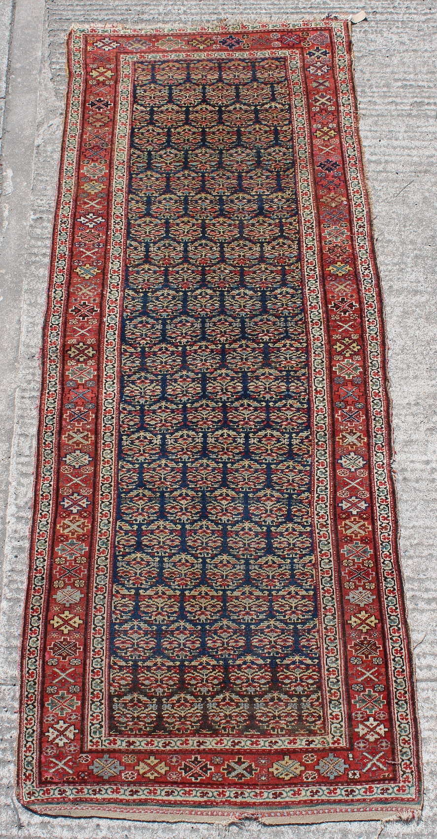 Property of a lady - an early 20th century Kurdish long rug, 116 by 42ins. (294 by 107cms.).