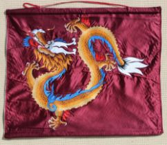 An embroidered silk wall hanging depicting a dragon on a burgundy ground, 26 by 31ins. (66 by 78cms.