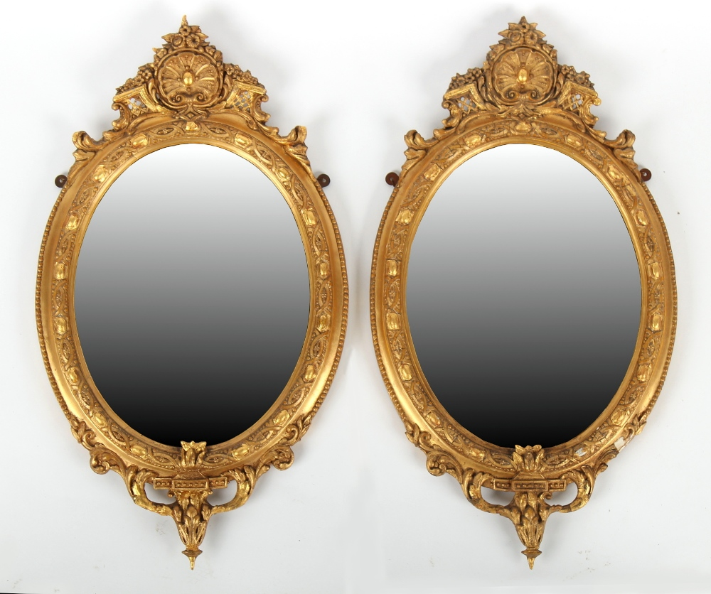 Property of a gentleman - a pair of Victorian gilt framed oval wall mirrors with bevelled glass