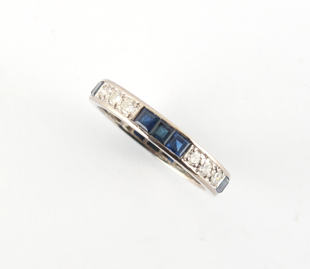 A platinum sapphire & diamond eternity ring, set with alternating rows of three square cut sapphires