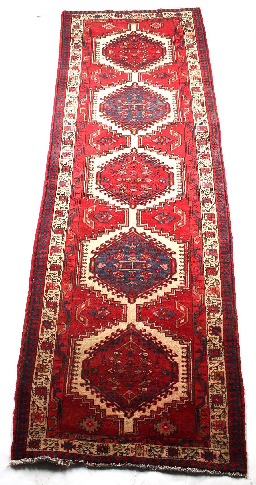 An Azari woollen hand-made runner, with red ground, 134 by 47ins. (340 by 107cms.).
