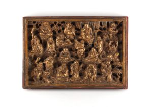 A Chinese carved giltwood & painted panel depicting eighteen various deities & figures, late 19th /