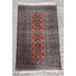 Property of a gentleman - a Tekke design hand knotted rug with red ground, 57 by 35ins. (146 by